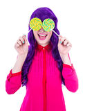 Happy woman with purple hair covering her eyes with two lollipop Stock Image