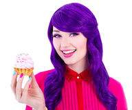 Happy woman with purple hair holding cupcake with pink cream iso Royalty Free Stock Images