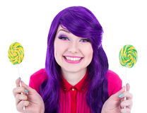 Happy woman with purple hair holding two lollipops isolated on w Royalty Free Stock Images