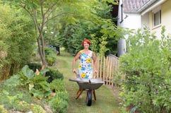 Happy Woman Pushing a Wheelbarrow with Tools Royalty Free Stock Photos