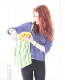 Happy woman put fruit in eco friendly cloth bag. Cheerful young woman putting bananas in reusable eco friendly shopping bag Stock Image