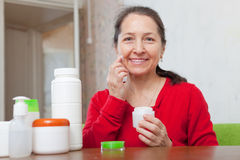Happy  woman puts cream on face Royalty Free Stock Photography