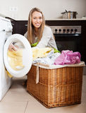 Happy  woman putting clothes in to washing machine Stock Images