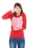 Happy woman putting a coin to piggybank. Royalty Free Stock Photo