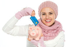 Happy woman putting credit card in piggy bank. Happy woman in knit winter clothing putting credit card in piggy bank Royalty Free Stock Photo