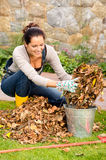 Happy woman putting dry leaves bucket yard Stock Photos