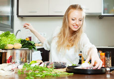 Happy woman putting  fish in flour into frying pan Stock Photos