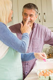 Happy woman putting flour on husbands nose. Happy women putting flour on husbands nose at home in the kitchen Royalty Free Stock Photo