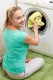 Happy woman putting laundry into washer at home Stock Photography