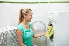 Happy woman putting laundry into washer at home Stock Images