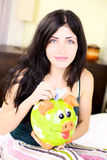 Happy woman putting money in piggy bank Stock Images