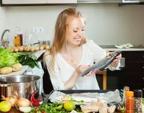 Happy woman putting  saltwater fish into sheet pan Stock Image