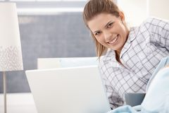 Happy woman in pyjama using laptop Royalty Free Stock Photography