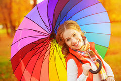 Happy woman with rainbow multicolored umbrella under rain in par Royalty Free Stock Images