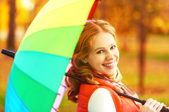 Happy woman with rainbow multicolored umbrella under rain in par. Happy woman with rainbow multicolored umbrella under rain on nature in the park Royalty Free Stock Photo