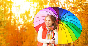 Happy woman with rainbow multicolored umbrella under rain in par. Happy woman with rainbow multicolored umbrella under rain on nature in the park Royalty Free Stock Images