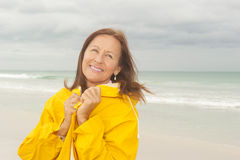 Happy Woman raincoat autumn season at beach Stock Photo
