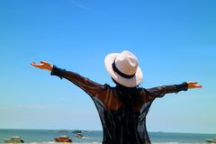 Happy woman raising arms enjoy beautiful sunny day at the sea royalty free stock photo