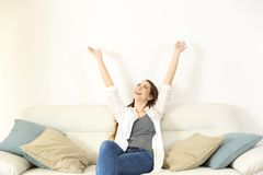 Happy woman raising arms and looking above on a couch. Wide angle view portrait of a happy woman raising arms and looking above on a couch with copy space royalty free stock photo