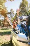Happy woman raising arms through the window car Stock Photography
