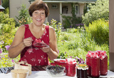 Happy woman with raspberry jam Royalty Free Stock Photo