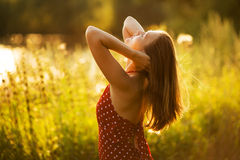 Happy woman in the rays of the evening sun Stock Photo