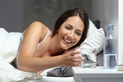 Happy woman reaching a glass of water in the night. Happy woman reaching a glass of water lying on the bed in the night at home royalty free stock images