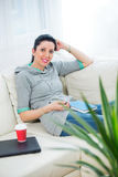 Happy woman read book on sofa in living room Royalty Free Stock Photos