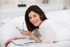 Happy woman reading in bed Stock Image