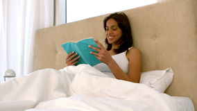 Happy woman reading in bed stock video footage