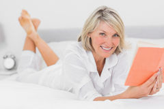 Happy woman reading a book lying on bed Stock Images