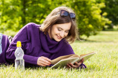 Happy woman reading book lying down on grass Royalty Free Stock Images