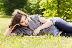 Happy woman reading book lying down on grass Stock Image