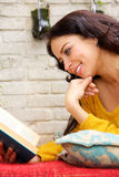 Happy woman reading book and lying outside Royalty Free Stock Photography