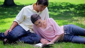 Happy woman reading a book near her boyfriend stock footage