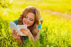 Happy  woman reading book outdoors Stock Photo
