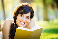 Happy woman reading book in park Stock Photography