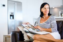 Happy woman reading a book sitting on a sofa Stock Images