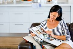 Happy woman reading a book sitting on a sofa Royalty Free Stock Photography