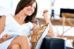 Happy woman reading a book sitting on a sofa stock photo