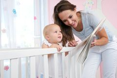 Happy woman reading a book to a cute baby Stock Image