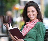 Happy woman reading and drinking coffee at an outdoor cafe Royalty Free Stock Photo
