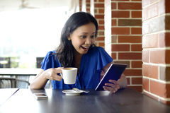 Happy woman reading email in Cafe. Happy young woman holding cup and reading email on tablet in Cafe Royalty Free Stock Photos