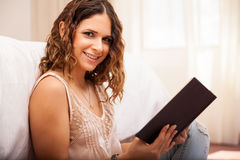 Happy woman reading at home. Beautiful young Latin woman reading a book and smiling while relaxing at home Stock Images