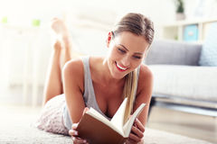 Happy woman reading at home. Picture showing happy woman reading at home Stock Image