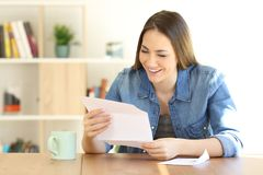 Happy woman reading a letter at home. Happy woman reading a letter on a table at home Royalty Free Stock Photo