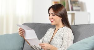 Happy woman reading a letter at home stock footage