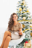 Happy woman reading magazine near christmas tree Stock Photography