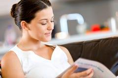 Happy woman reading a magazine sitting on a sofa Royalty Free Stock Photo