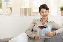 Happy woman reading newspaper on sofa Royalty Free Stock Photography